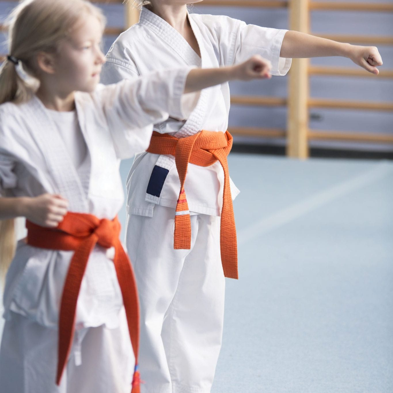 Young girls wearing orange belts, training moves and looking in the direction of their coach during karate classes